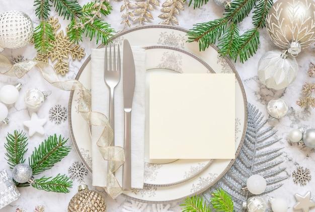 装飾品モミの木の枝と正方形の空白のカードの上面図モックアップとお祝いのテーブルの設定