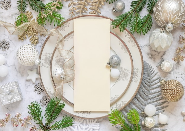 Festive table setting with ornaments and fir tree branches top view. mockup of christmas or new year menu card on white marble table flat lay, copy space. winter season, restaurant holiday catering