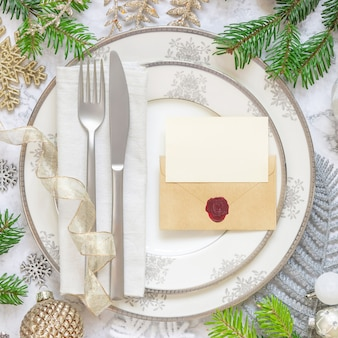 Festive table setting with pastel decorations fir tree branches blank card and envelope mockup
