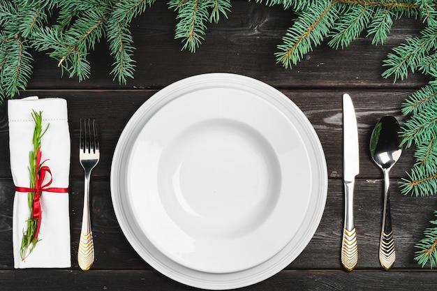 Festive table setting with pine tree branches on wooden background