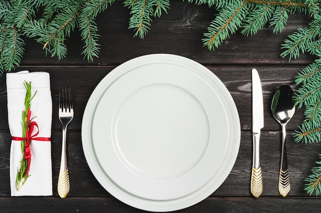 Festive table setting with pine tree branches on wooden surface