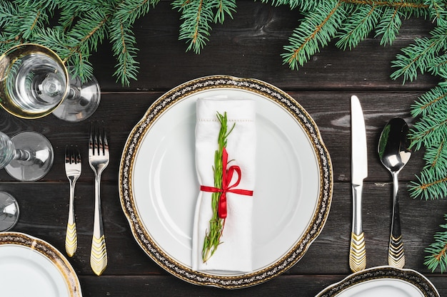 Festive table setting with pine tree branches on wooden table