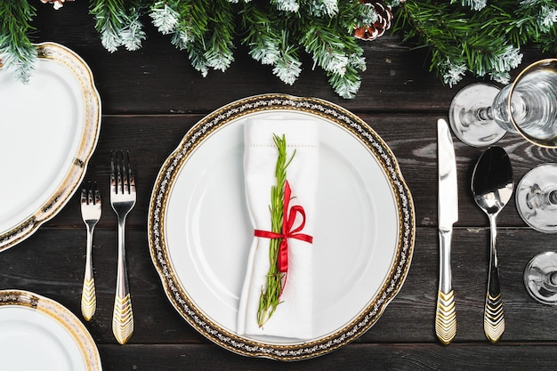 Festive table setting with pine tree branches on wooden