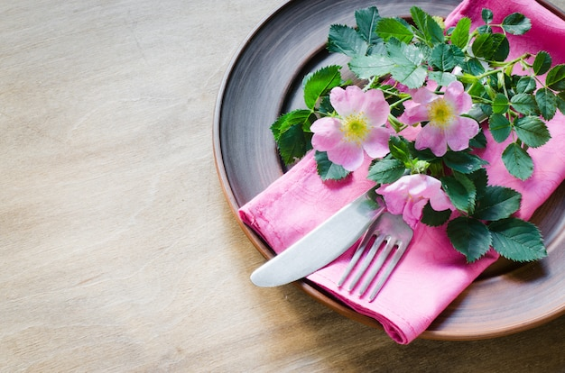 Festive table setting with pink flowers.