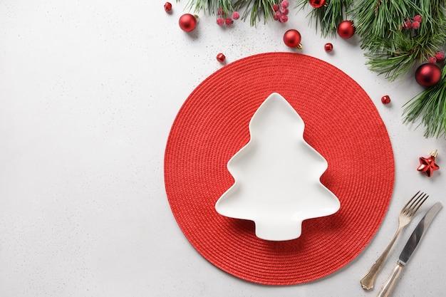 Сервировка праздничного стола с тарелкой в форме рождественской елки на белом фоне с красным украшением. вид сверху. место для текста.