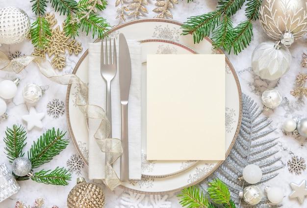 プレートカトラリーの装飾品とモミの木の枝の上面図とお祝いのテーブルの設定