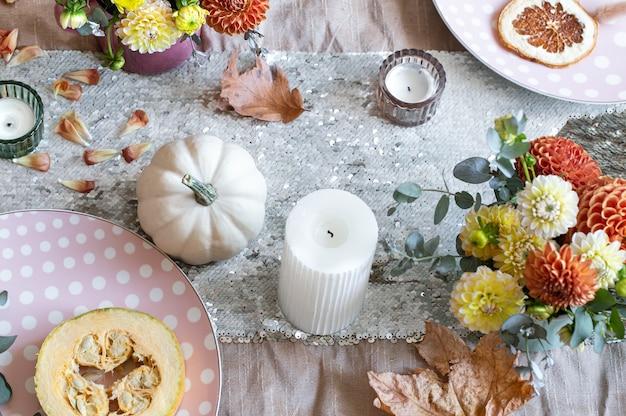 カボチャのキャンドルと菊の花でお祝いのテーブルセッティング