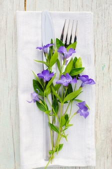 Festive table setting with purple flowers.