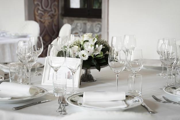 明るい色のバラとベージュのテーブルにヴィンテージの食器を置いたお祝いのテーブルセッティング。イベントパーティーや結婚披露宴用のテーブルセット。