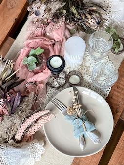 ドライフラワーの小枝と装飾的な要素を備えたお祝いのテーブルセッティング。