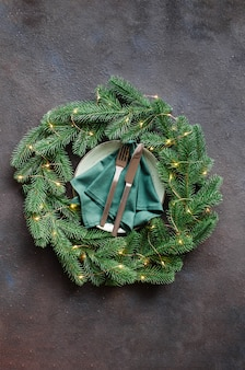 Festive table setting with xmas decorations in the form of a christmas wreath.