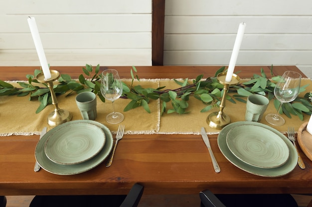 Сервировка праздничного стола, деревянный стол с зелеными тарелками и весенними травами. фото высокого качества