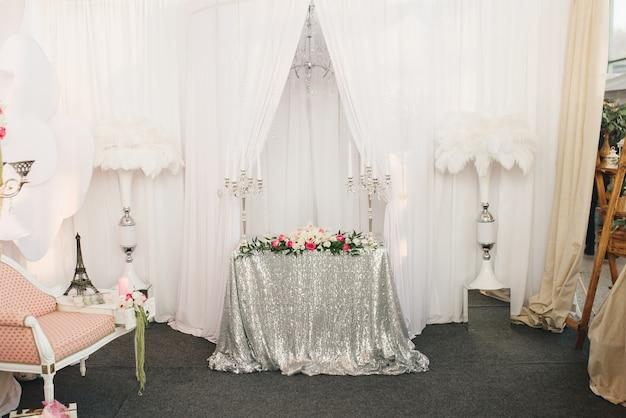 꽃병 옆에 스팽글의 은색 식탁보가있는 축제 테이블은 흰색 타조 깃털입니다. 결혼식 장식, 전시회, 생일, 장식