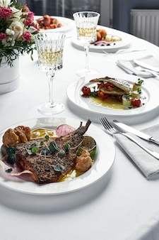 Festive table with fish dishes and glasses of wine, grilled flounder sea bass on a light table with white wine, wedding table concept.