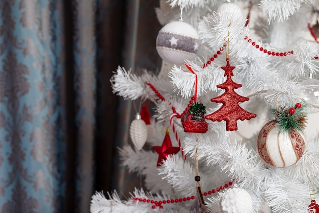 Festive toys on a white christmas tree. christmas and new year. copy space