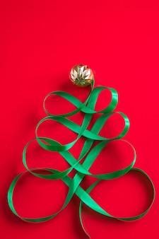赤い背景の上のサテンの緑のリボンで作られたお祭りの木クリエイティブなクリスマスのコンセプト