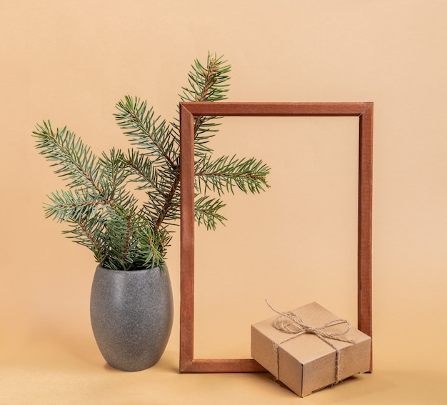Festive trendy minimal composition with fir tree branches in grey stone vase, empty wooden frame and cardboard gift box on beige background. christmas or new year mock up. square photo.