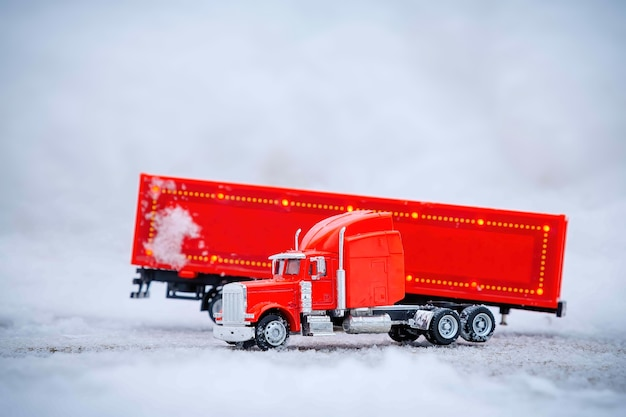 빨간 장난감 자동차의 축제 트럭이 분리된 화물 컨테이너와 함께 서 있습니다. 겨울 크리스마스 휴일