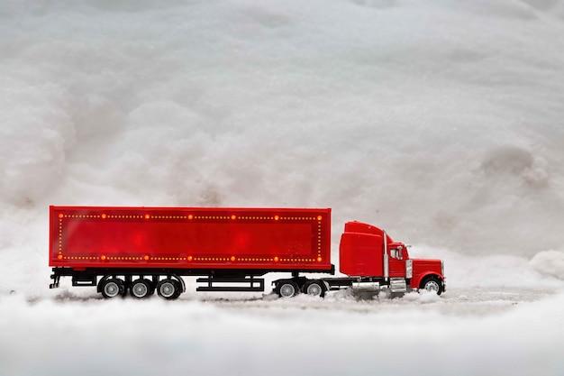 빨간 장난감 자동차의 축제 트럭은 실제 눈 더미를 타고 겨울 크리스마스 휴가를 보냅니다.