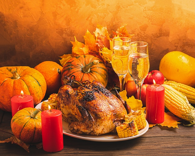 Festive turkey or chicken baked by thanksgiving two glasses of wine harvest of seasonal vegetables on a rustic table.