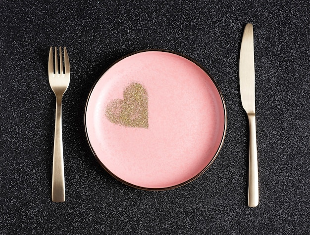 Festive valentine's day table setting, pink plate with golden hearts on black shiny background