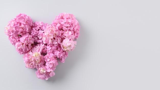 灰色のハートの形をしたピンクのアジサイの花のお祝いバレンタインデーカード。愛の概念