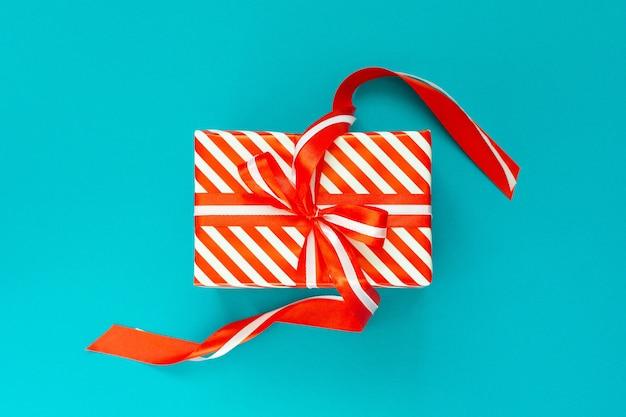 赤と白の縞模様の贈り物、青いターコイズ色の壁にリボンと弓の付いたギフト ボックス、トップ ビューでお祝いの壁