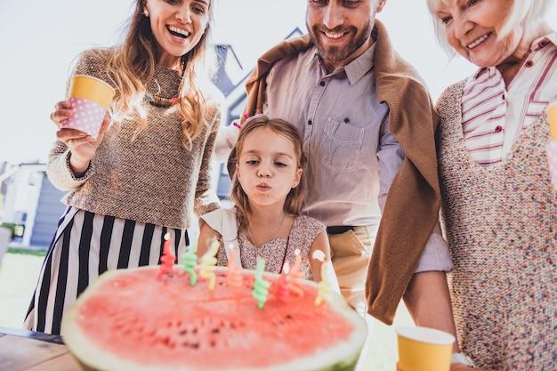 축제 수박. 그들의 딸을 보면서 얼굴에 미소를 유지하는 행복한 사람들