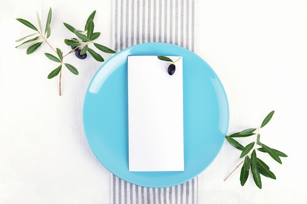 Festive wedding, birthday table setting with golden cutlery, olive branch, pastel blue porcelain plate. blank card. restaurant menu concept