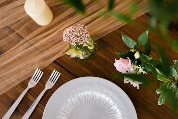 Праздничная свадьба, праздничная сервировка стола серебряными столовыми приборами, тюлевой лентой, ветками эвкалипта, цветами эустомы и гиацинтами. концепция меню ресторана. плоская планировка, вид сверху