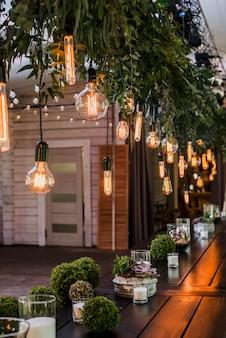 Праздничный свадебный стол с гирляндами эдисона, висящими на кружевах, украшенных зелеными цветочными ветками зернистый эффект