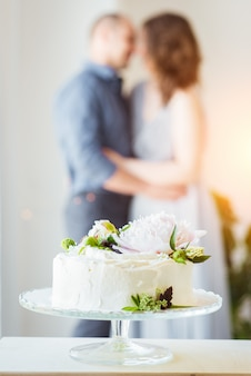 Festive white cake on a stand and a couple in love