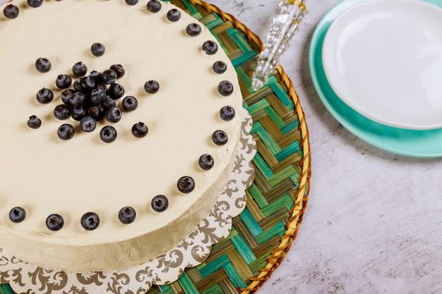 白いテーブルに新鮮なブルーベリーとお祝いの白いケーキ
