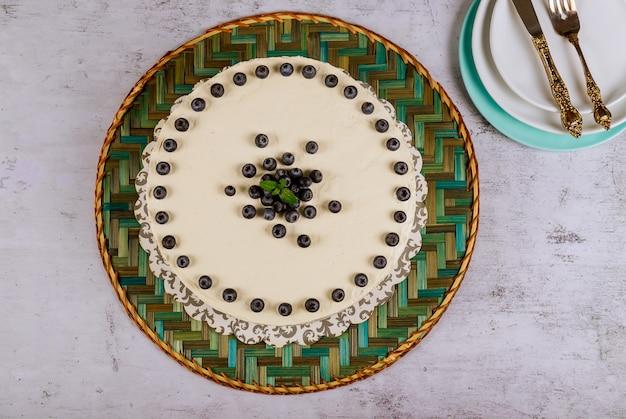 白いテーブルにホイップクリームと新鮮なブルーベリーとお祝いの白い丸いケーキ