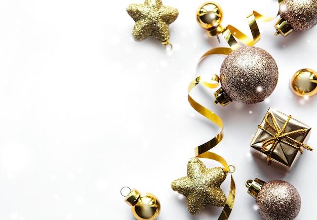 Праздничная белая поверхность с золотыми елочными украшениями