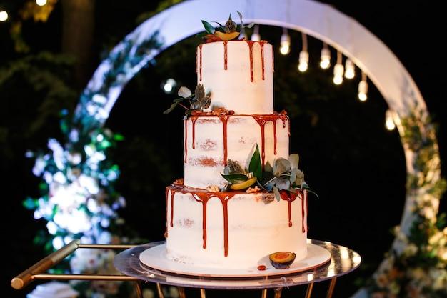 お祝いの白い3層のウエディングケーキ
