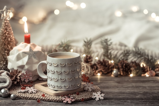 Festive with cup on wood with lights and festive decor. coziness and comfort at home