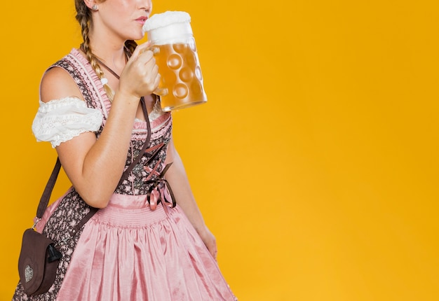 Festive woman in costume ready to drink beer