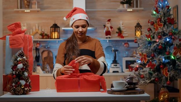 Праздничная женщина готовит подарки с оберточной бумагой