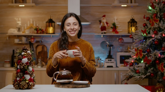 Festive woman talking on video call conference with family