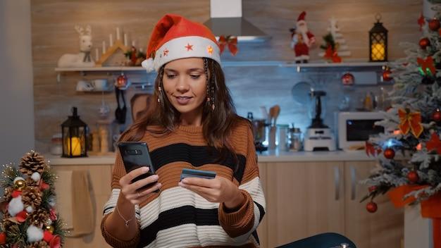 Праздничная женщина, использующая смартфон для покупок подарков
