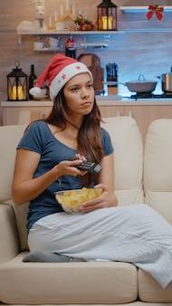 テレビを見て、ボウルからチップを食べるお祭りの女性