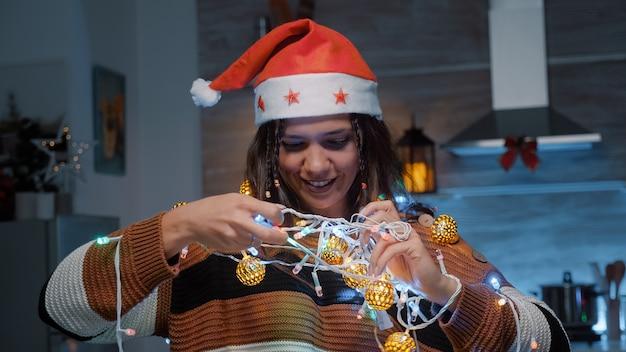 Праздничная женщина в новогодней шапке пытается распутать огни