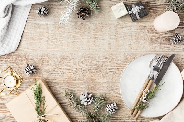Festive wooden table setting with winter decorations, cutlery, candles and gifts. top view, flat lay. the concept of a christmas family dinner.