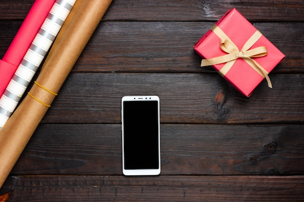 Festive wrapping paper, pink gift and white phone on a dark background. view from above.