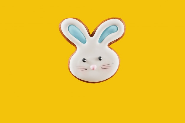 Festive yellow background with cookie in shape of easter bunny