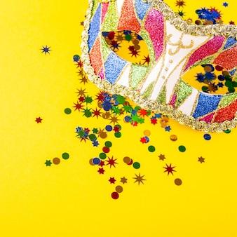 화려한 카니발 마스크 축제 노란색 표면입니다. 생일, 카니발, 파티에 대한 인사말 카드 개념. 복사 공간, 평면도, 평면 위치