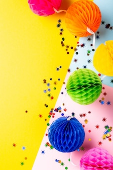 Праздничная желтая поверхность с красочными бумажными шарами. концепция поздравительной открытки для дня рождения, вечеринки, приглашения, карнавала. копирование пространства, вид сверху, плоская планировка