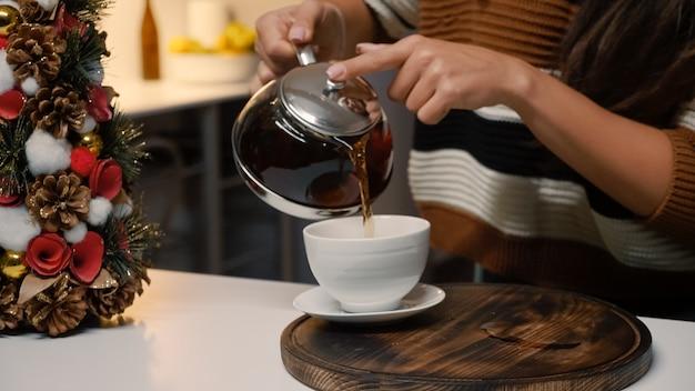 Giovane donna festosa che versa il tè dal bollitore in tazza