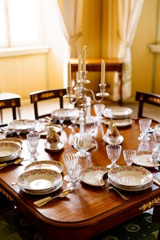 A festively decorated fish table with clean empty plates spoons knives wine glasses decanters